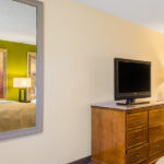 Quality Inn & Suites Laurel guest room with one bed and TV with dresser